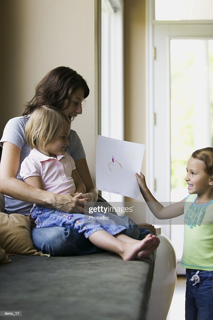 lifestyle shot of a mother sitting with a child as her other daughter shows her some artwork : Stockfoto