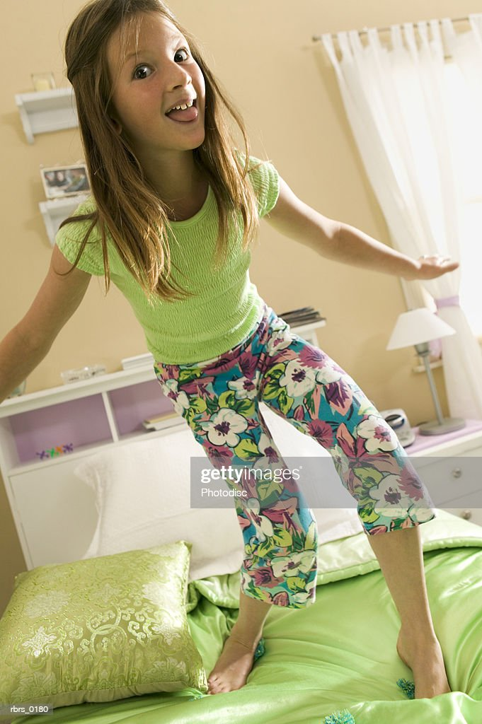 lifestyle shot of a teenage female as she plays and jumps on her bed : Stockfoto