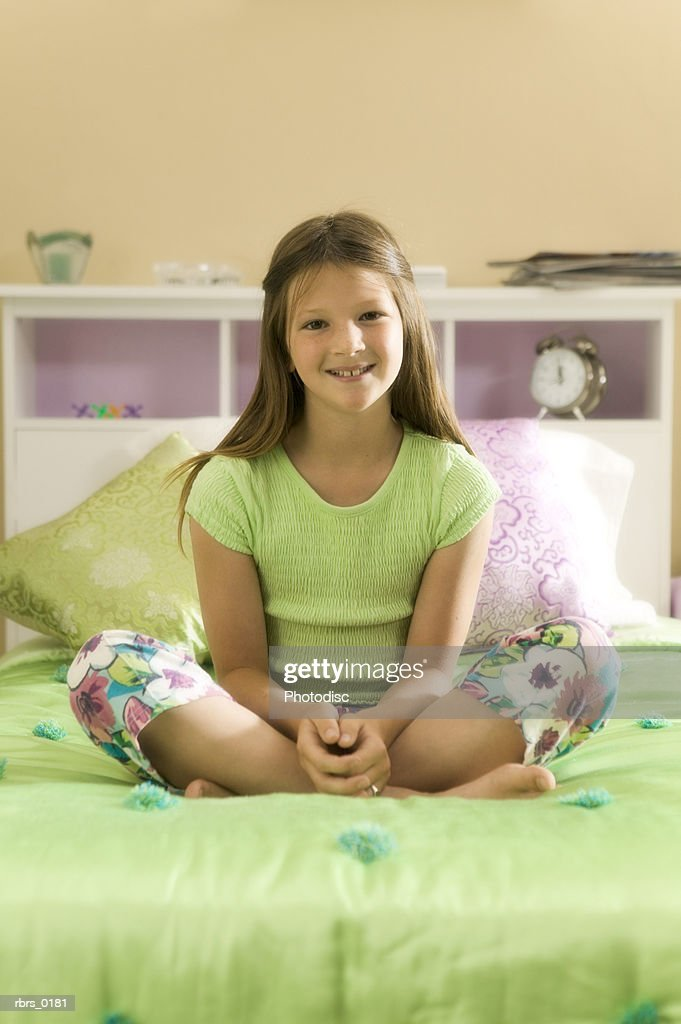 lifestyle shot of a teenage female as she sits on her bed and smiles : Foto de stock