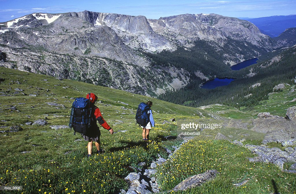 lifestyle shot of a two adult males as they climb down a mountain into a beautiful valley : Stockfoto