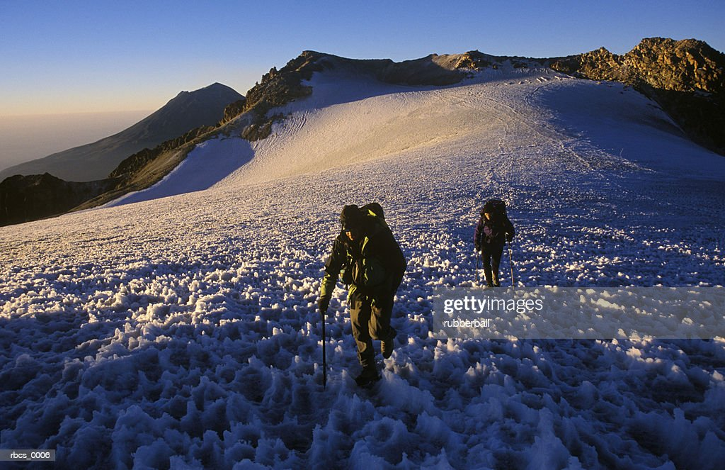 lifestyle shot of a two adult males as they slowly climb up a snow covered mountain : Stockfoto