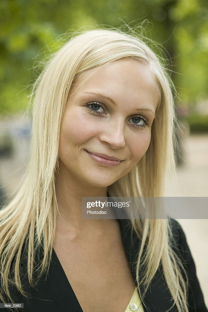 lifestyle shot of a young adult blonde woman as she smiles at the camera : Foto de stock