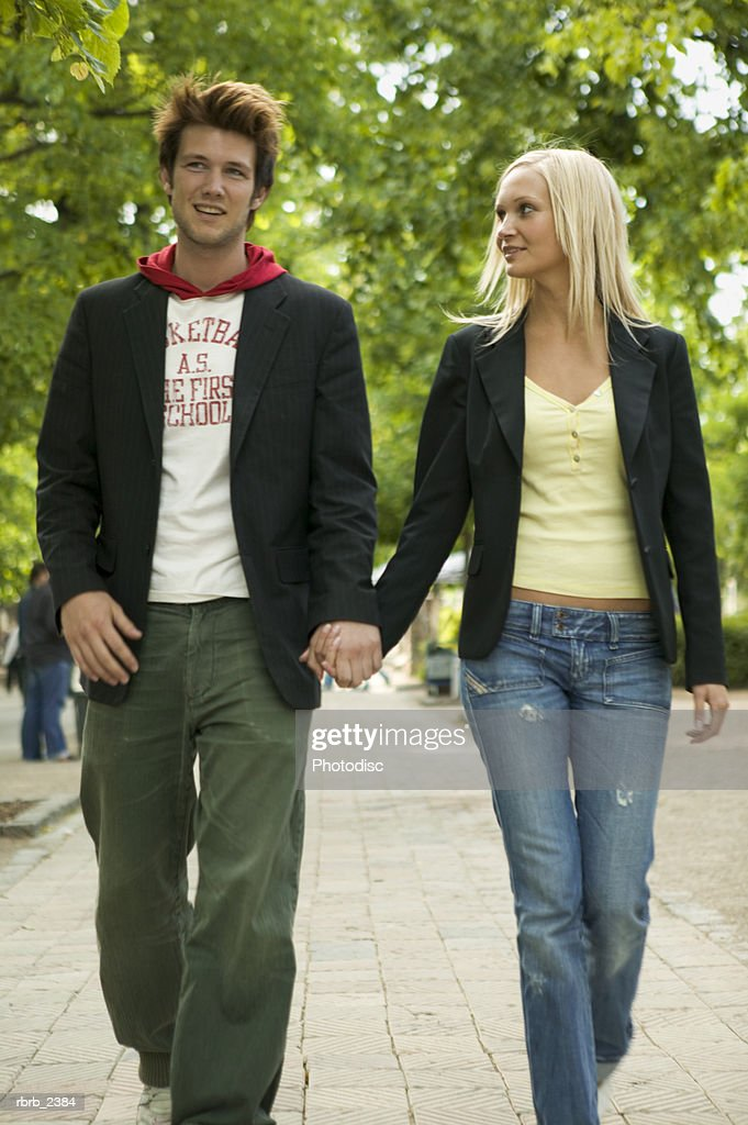 lifestyle shot of a young adult couple as they walk holding hands : Foto de stock