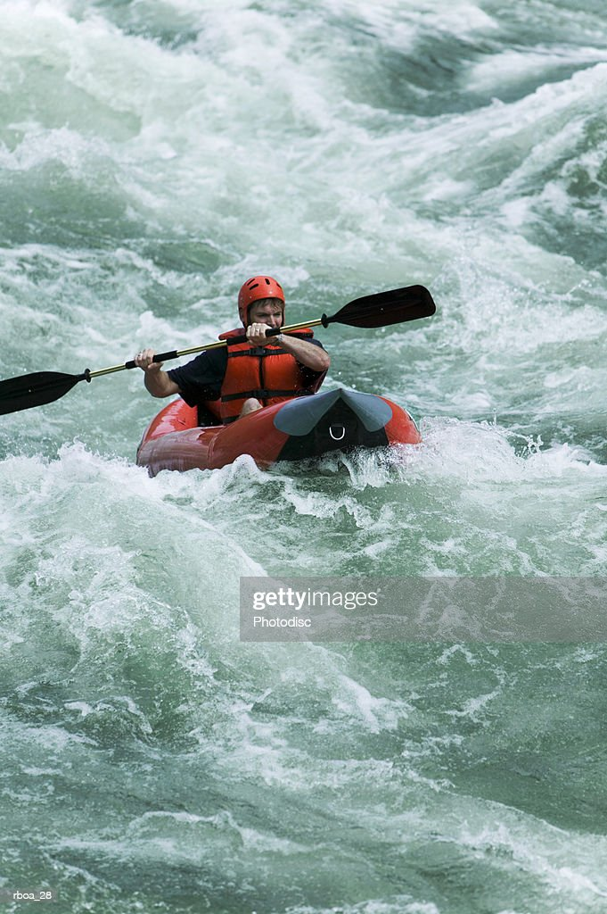 lifestyle shot of a young adult male as he rides a kayak down some river rapids : Stock Photo
