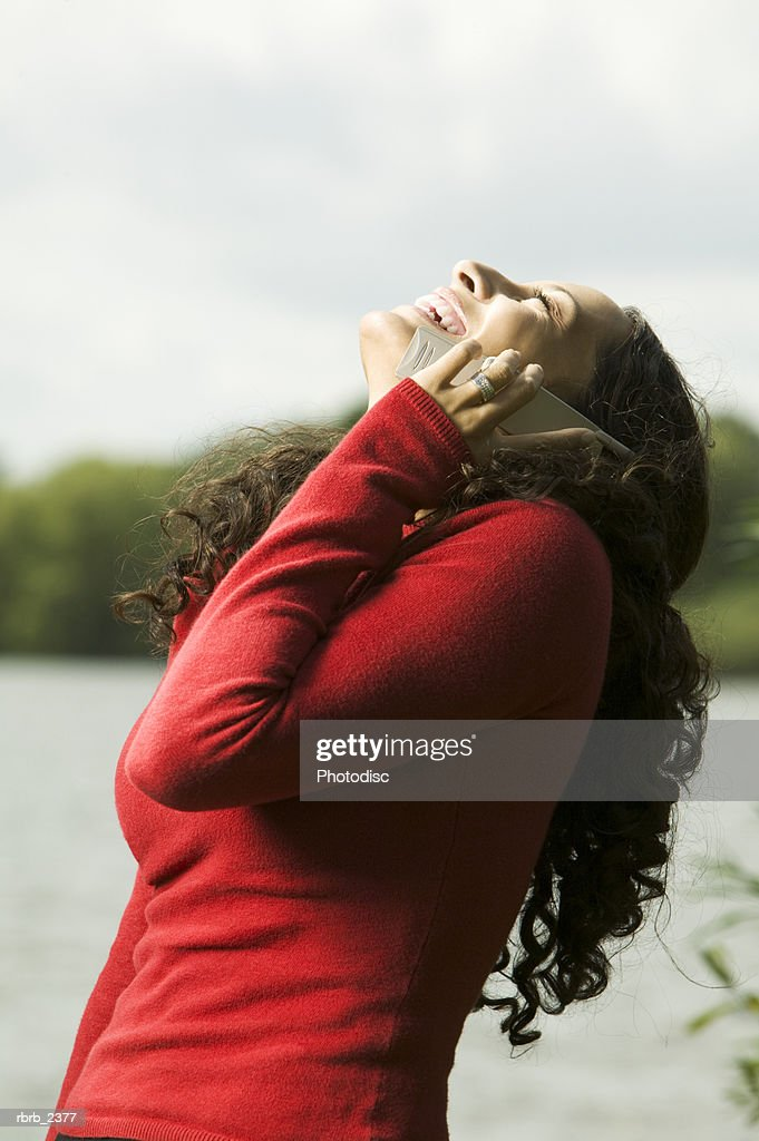 lifestyle shot of a young adult woman as she chats on a cell phone at the shore of a lake : Foto de stock