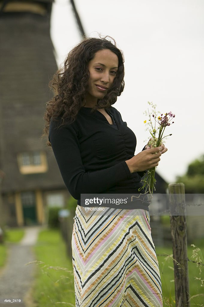 lifestyle shot of a young adult woman as she holds wild flowers in front of a windmill : Foto de stock