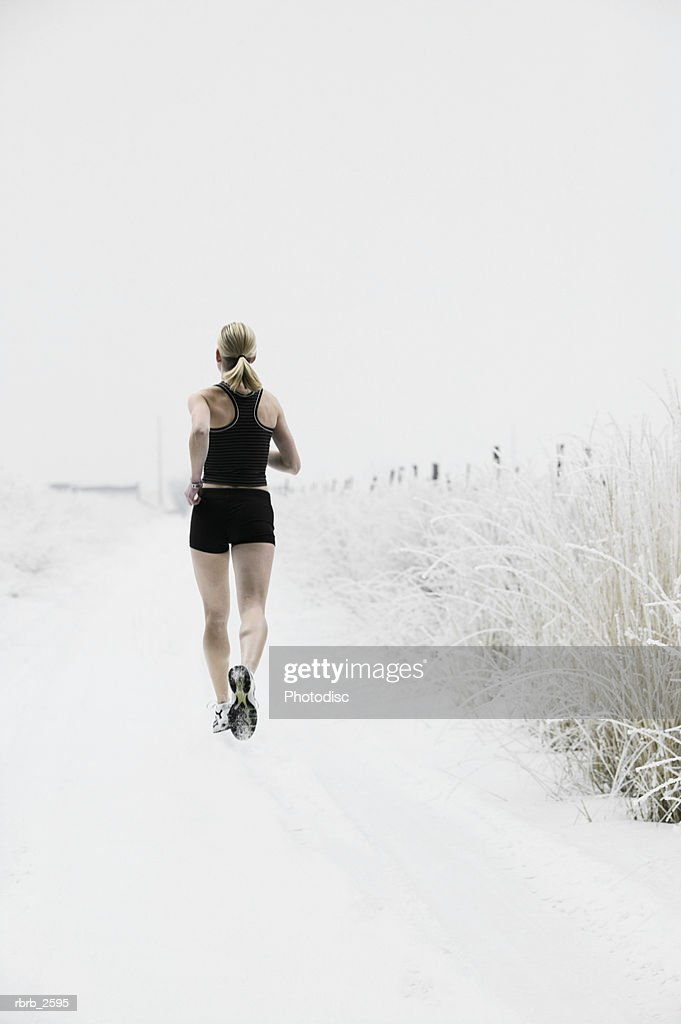 lifestyle shot of a young adult woman as she jogs down a snowy road : Foto de stock