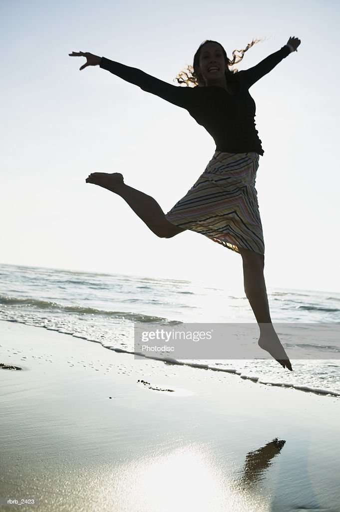 lifestyle shot of a young adult woman as she jumps through the air while on the beach : Foto de stock