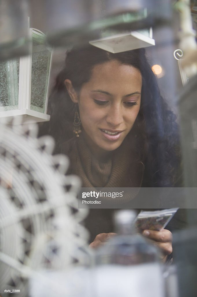 lifestyle shot of a young adult woman as she looks at items while window shopping : Foto de stock