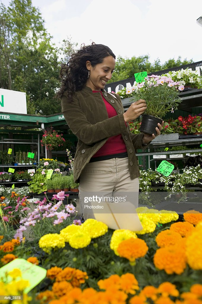 lifestyle shot of a young adult woman as she looks at various plants in an outdoor market : Foto de stock