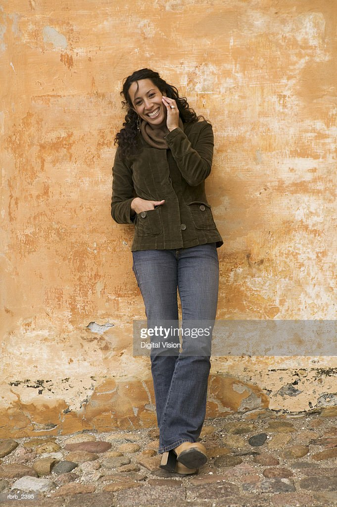 lifestyle shot of a young adult woman as she makes a call on a cell phone : Foto de stock