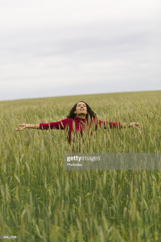 lifestyle shot of a young adult woman as she outstretches her arms in the middle of tall green grass : Foto de stock