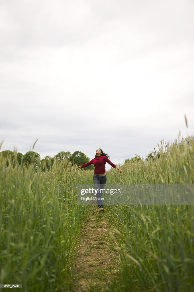 lifestyle shot of a young adult woman as she playfully runs down a path through tall green grass : Stockfoto