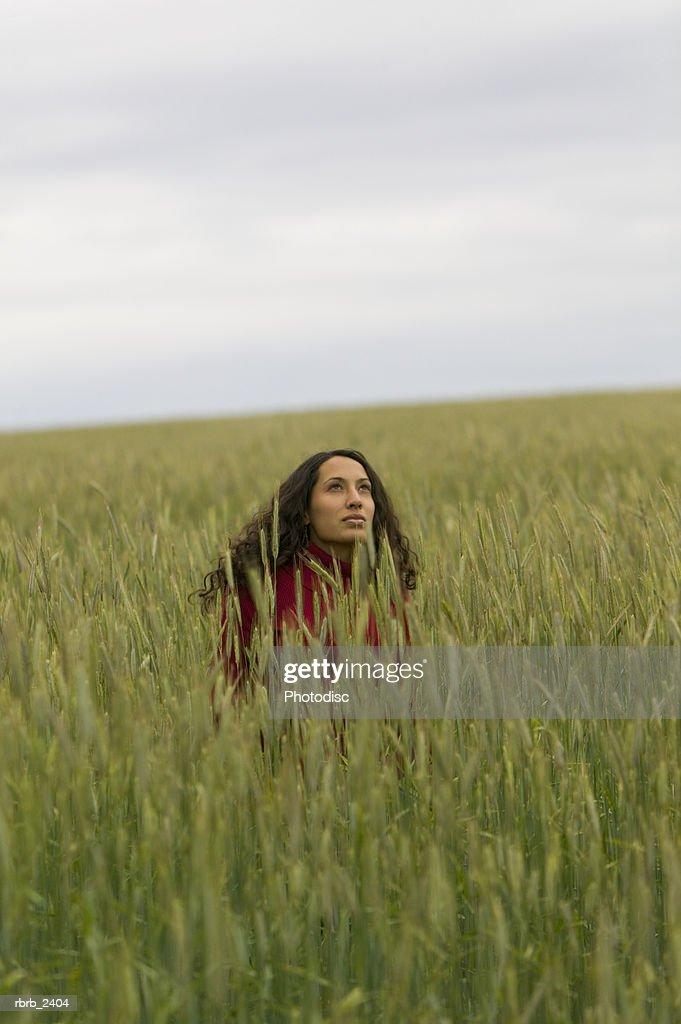 lifestyle shot of a young adult woman as she plays in very tall green grass : Foto de stock