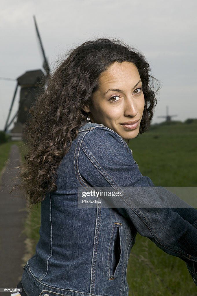 lifestyle shot of a young adult woman as she poses in front of an old world windmill : Foto de stock