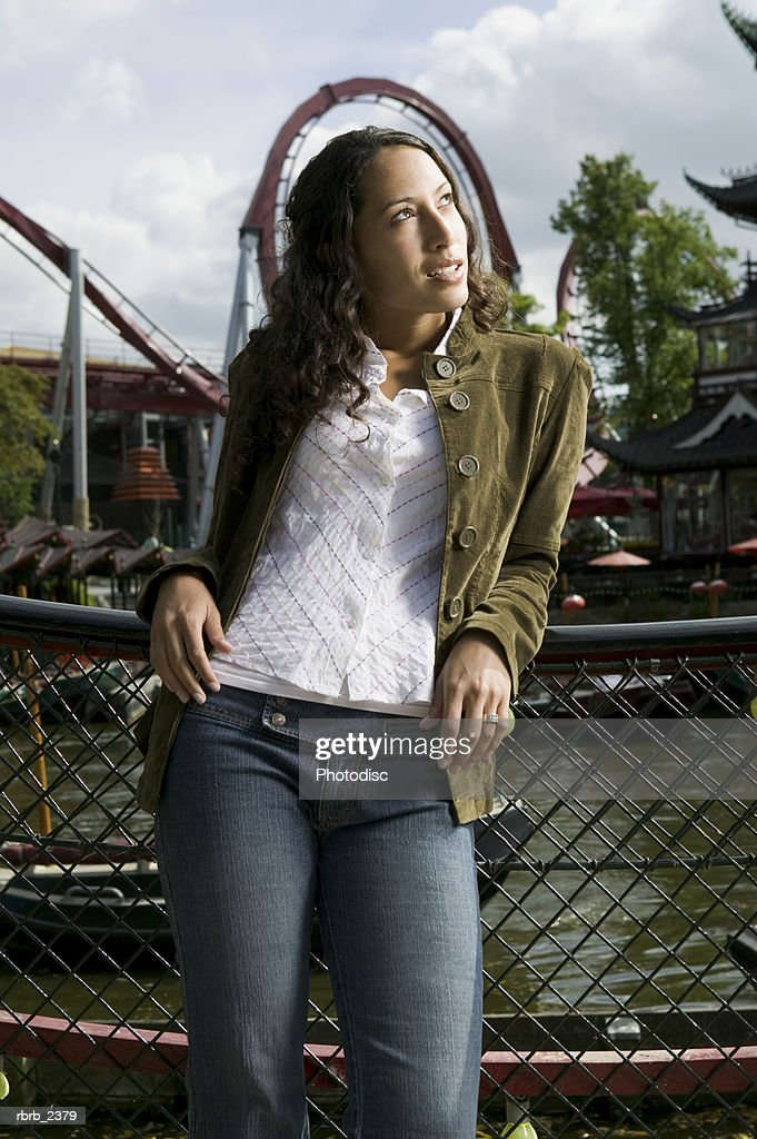 lifestyle shot of a young adult woman as she poses under a roller coaster : Foto de stock