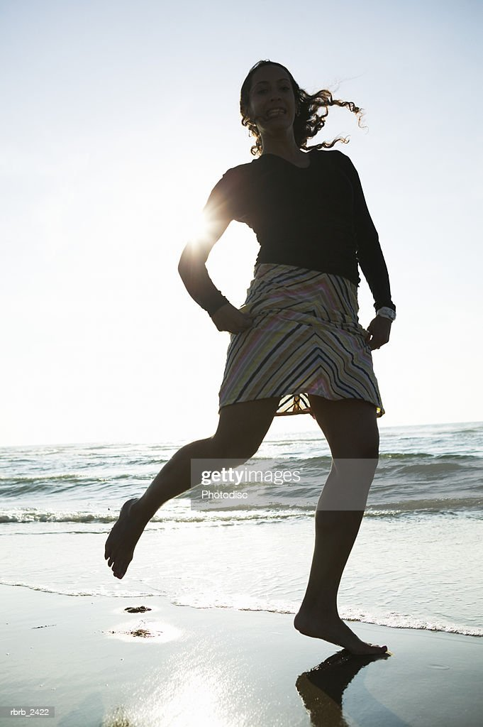 lifestyle shot of a young adult woman as she runs and plays on the beach : Foto de stock