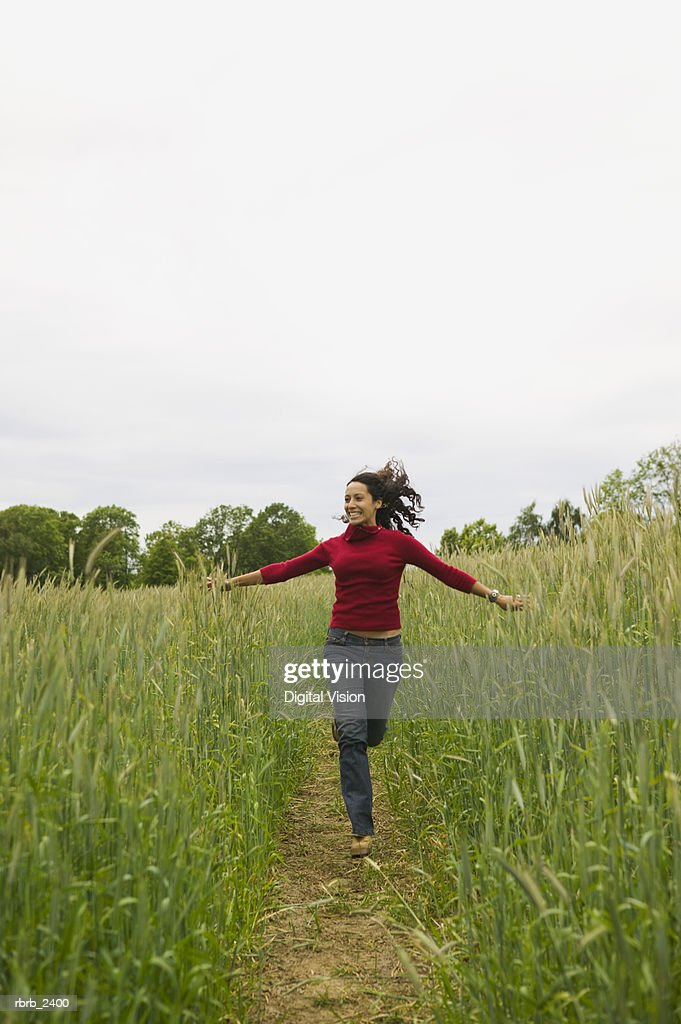 lifestyle shot of a young adult woman as she runs down a path through tall green grass : Foto de stock