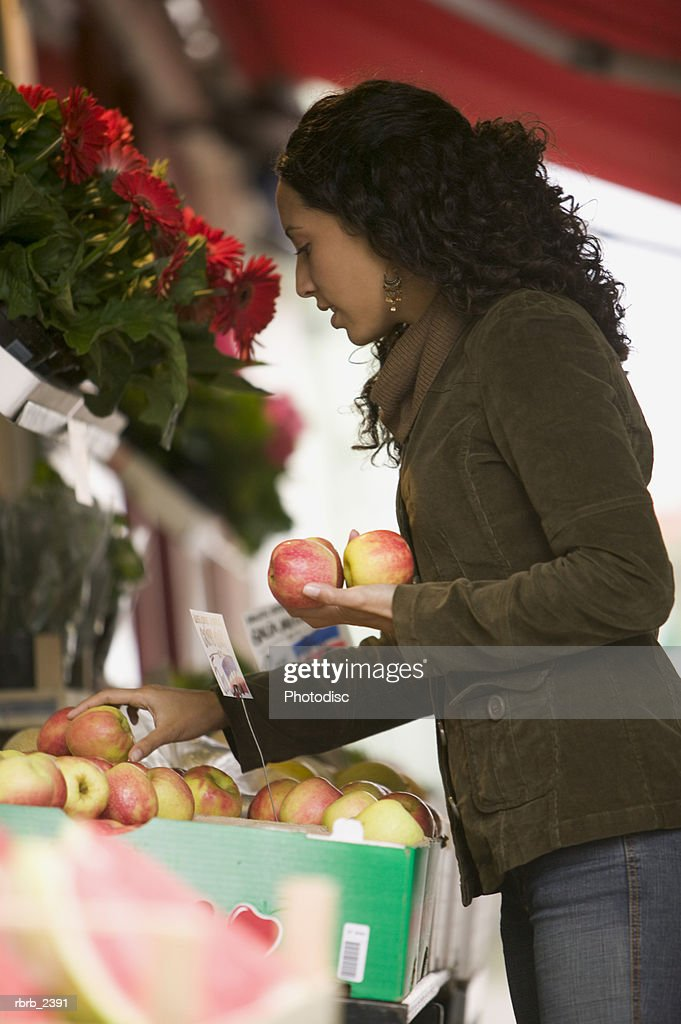 lifestyle shot of a young adult woman as she shops for fruit at an outdoor marketplace : Foto de stock