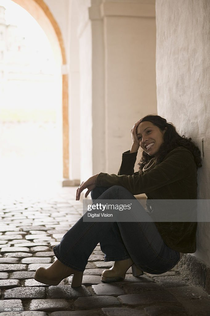 lifestyle shot of a young adult woman as she sits down and rests under an archway : Foto de stock