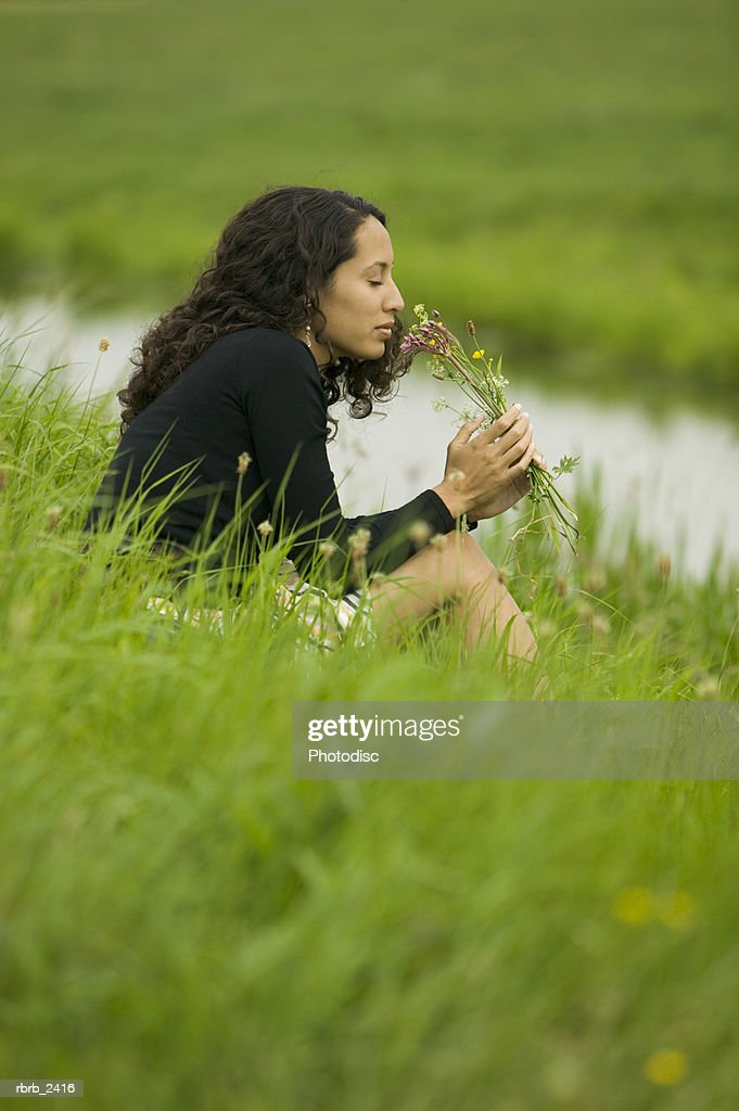 lifestyle shot of a young adult woman as she sits in grass by a stream and smells wild flowers : Foto de stock
