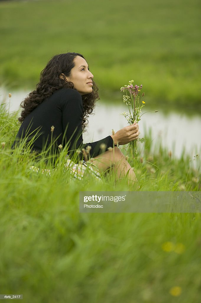 lifestyle shot of a young adult woman as she sits in grass by a stream holding wild flowers : Foto de stock