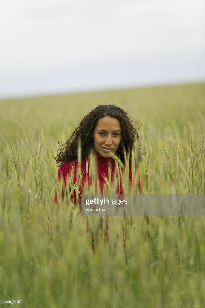 lifestyle shot of a young adult woman as she sits within a field of tall green grass : Foto de stock