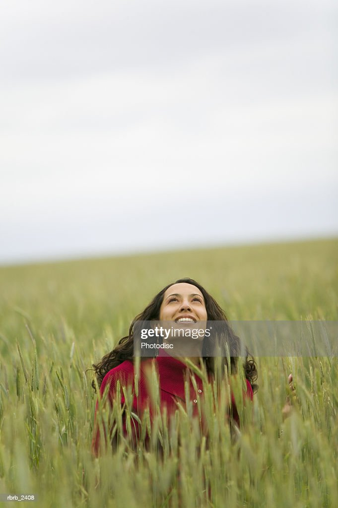 lifestyle shot of a young adult woman as she sits within a field of tall green grass and looks up : Foto de stock