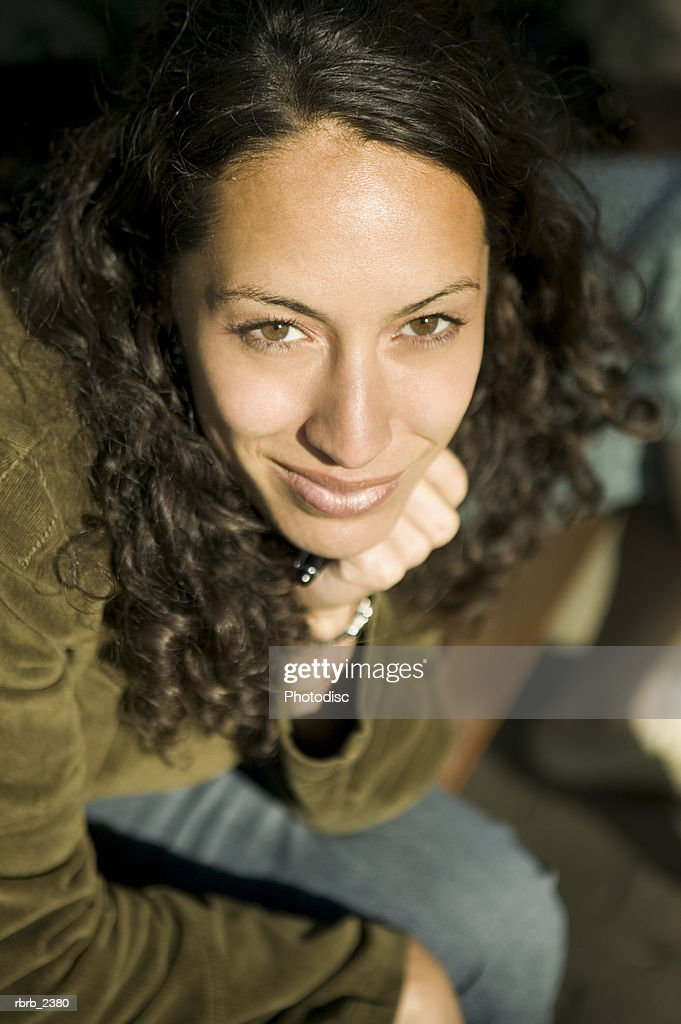 lifestyle shot of a young adult woman as she smiles up at the camera : Foto de stock