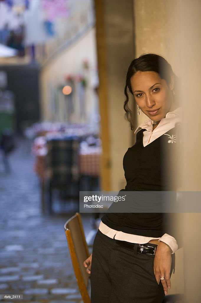 lifestyle shot of a young adult woman as she stands in front of an outdoor cafe : Foto de stock