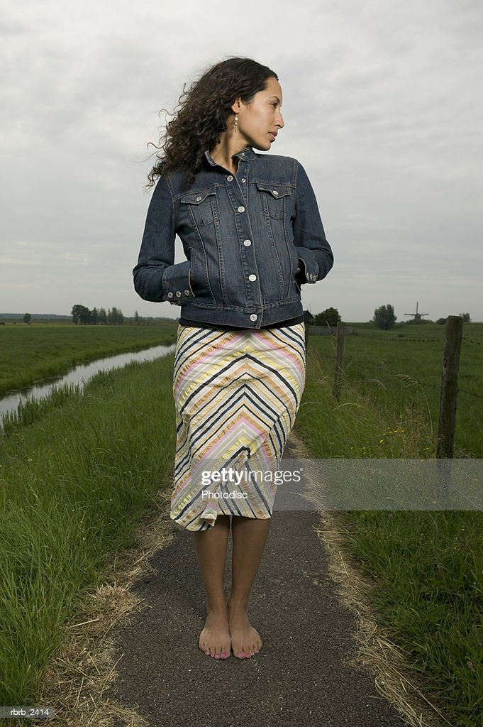 lifestyle shot of a young adult woman as she stands on a path that winds through a green open field : Foto de stock