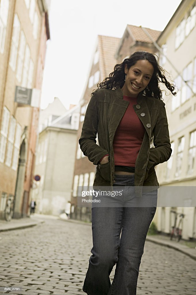 lifestyle shot of a young adult woman as she strolls down a european style street : Foto de stock