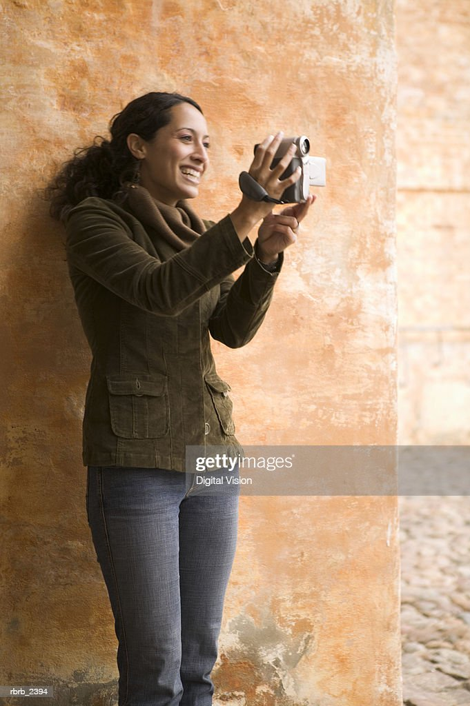 lifestyle shot of a young adult woman as she uses a digital video camera : Foto de stock