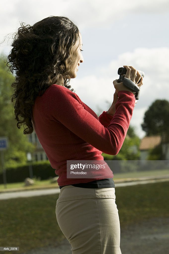 lifestyle shot of a young adult woman as she uses a video camera : Foto de stock