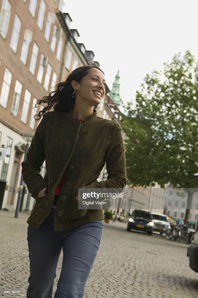 lifestyle shot of a young adult woman as she walks down a european style street : Foto de stock