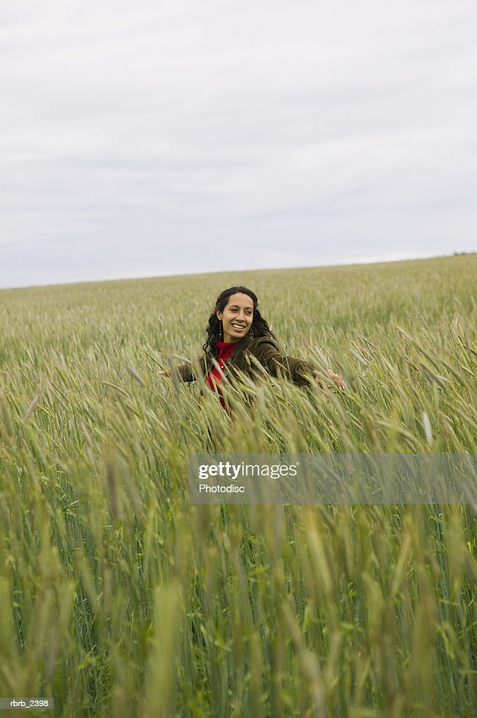 lifestyle shot of a young adult woman as she walks through tall green grass : Foto de stock