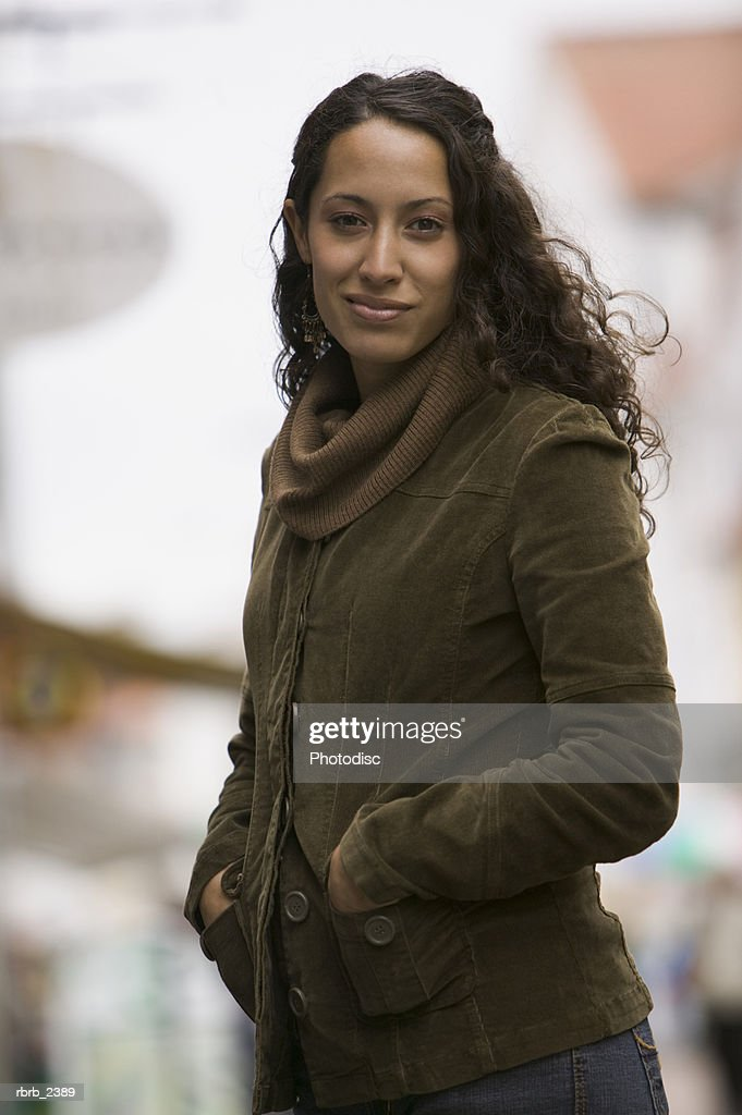 lifestyle shot of a young adult woman in a coat as she turns and smiles at the camera : Foto de stock