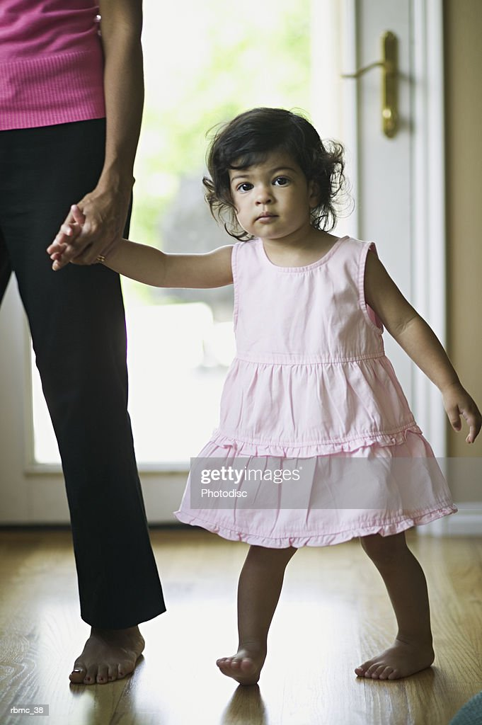 lifestyle shot of a young female toddler as she walks through her home led by her mother : Stockfoto