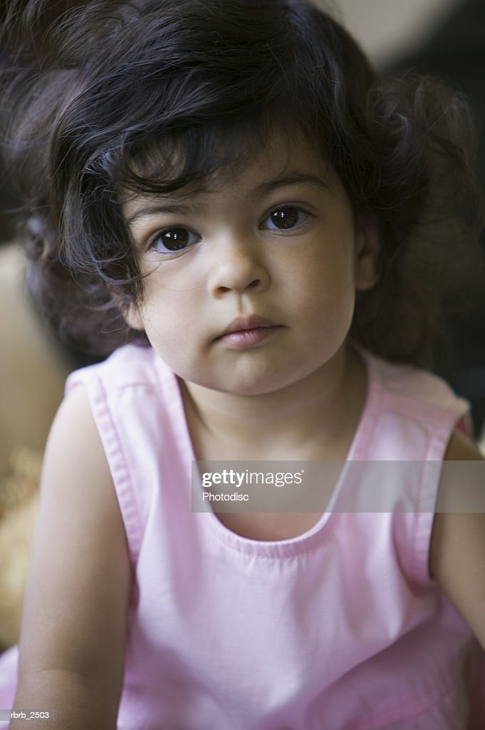 lifestyle shot of a young female toddler in a pink dress as she looks up at the camera : Foto de stock
