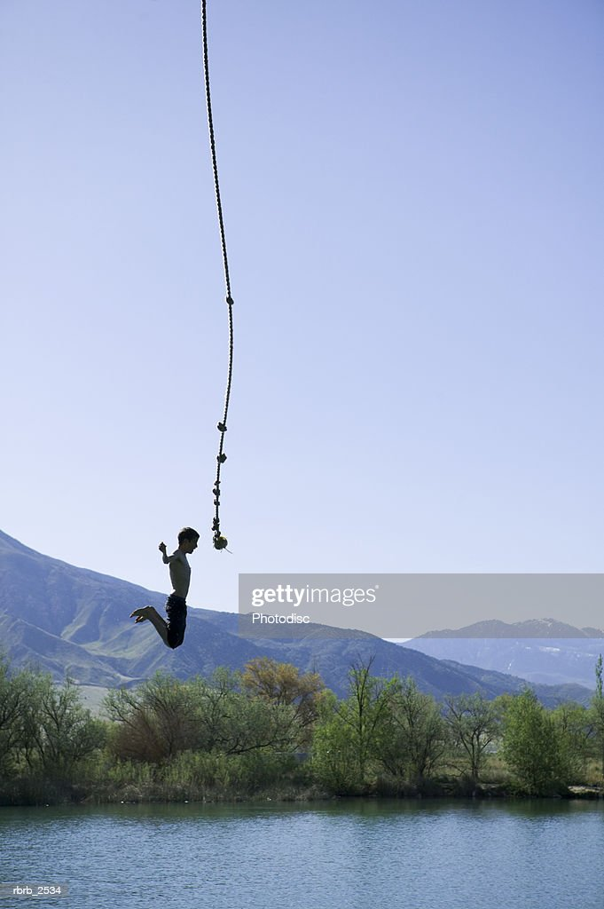 lifestyle shot of a young male as he swings on a rope and jumps into a pond : Foto de stock