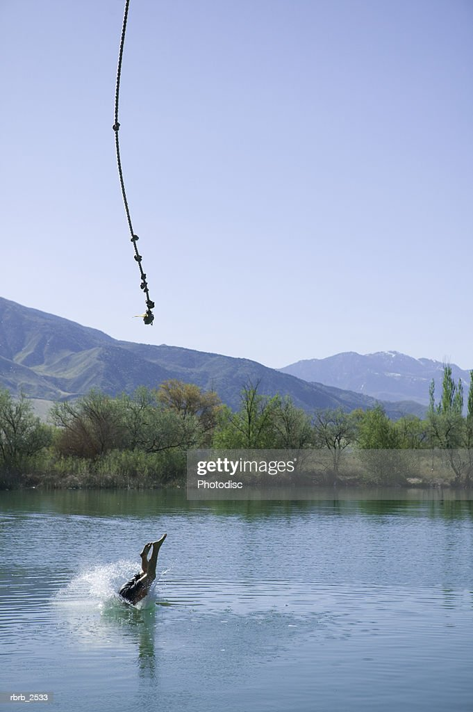 lifestyle shot of a young male as he swings on a rope and splashes into a pond : Foto de stock