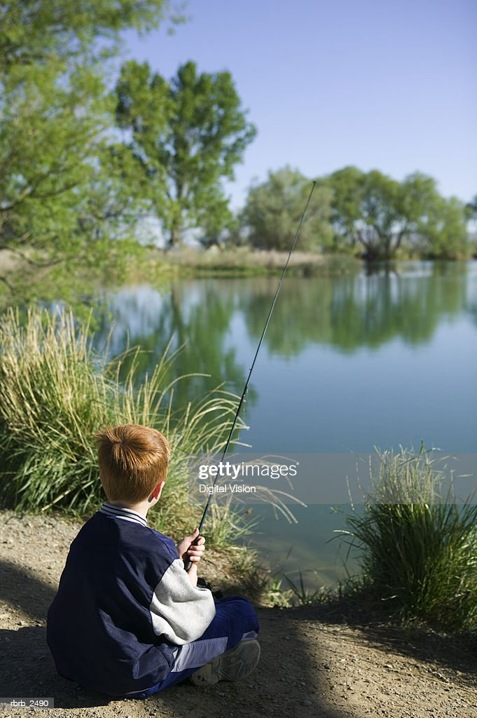 lifestyle shot of a young male child as he sits on the bank of a river and fishes : Foto de stock