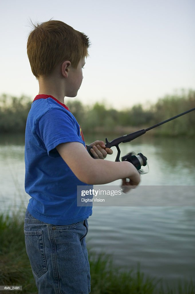 lifestyle shot of a young male child as he stands on the bank of a river and fishes : Stockfoto