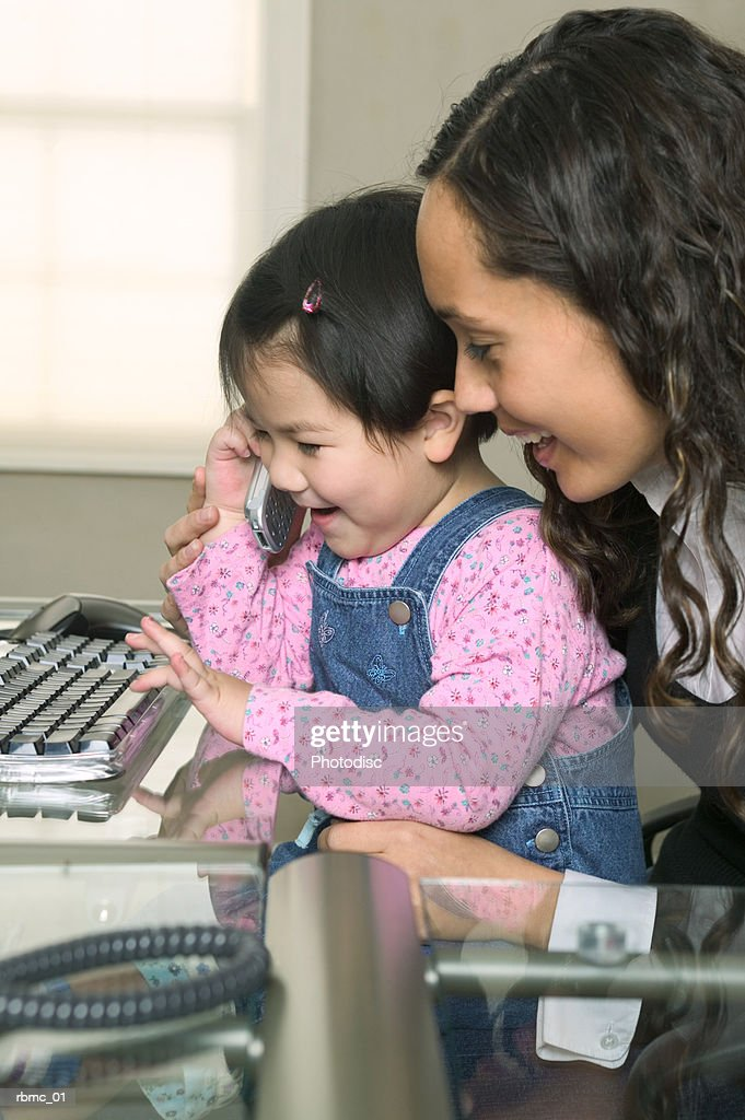 lifestyle shot of a young mother as she lets her daughter chat on a cell phone : Stockfoto