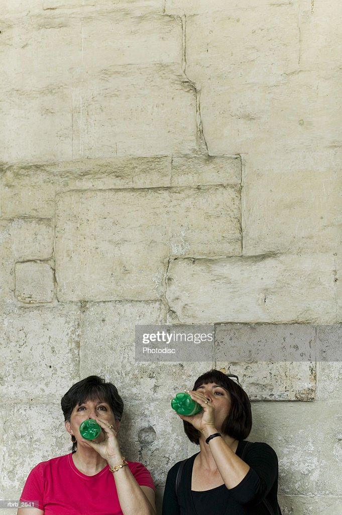 lifestyle shot of an adult daughter and her mother as they both drink a beverage : Foto de stock