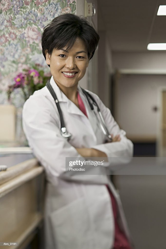lifestyle shot of an adult female doctor in a hospital hallway as she folds her arms and smiles : Foto de stock