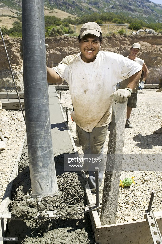 lifestyle shot of an adult male construction worker as he pours cement into a foundation : Foto de stock