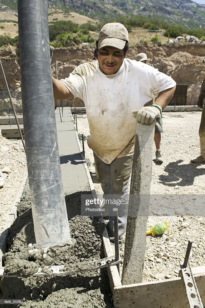 lifestyle shot of an adult male construction worker in work clothes as he pours cement : Foto de stock