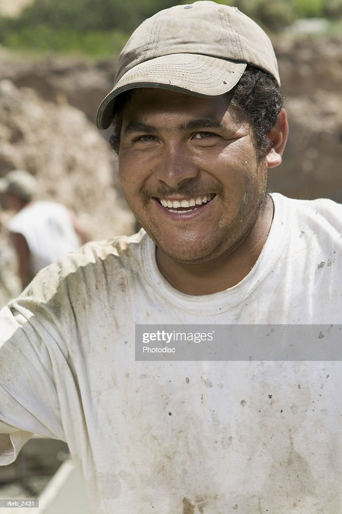 lifestyle shot of an adult male construction worker in work clothes as he smiles at the camera : Foto de stock