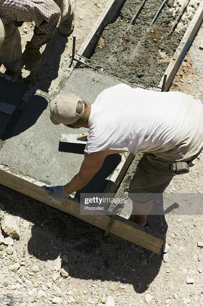 lifestyle shot of an adult male construction worker in work clothes as he lays cement : Foto de stock